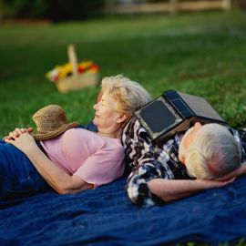 Seniors relaxing on picnic blanket