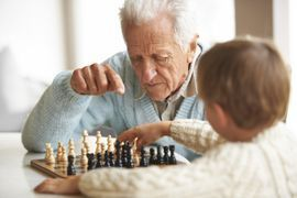 Grandfather playing chess with grandson